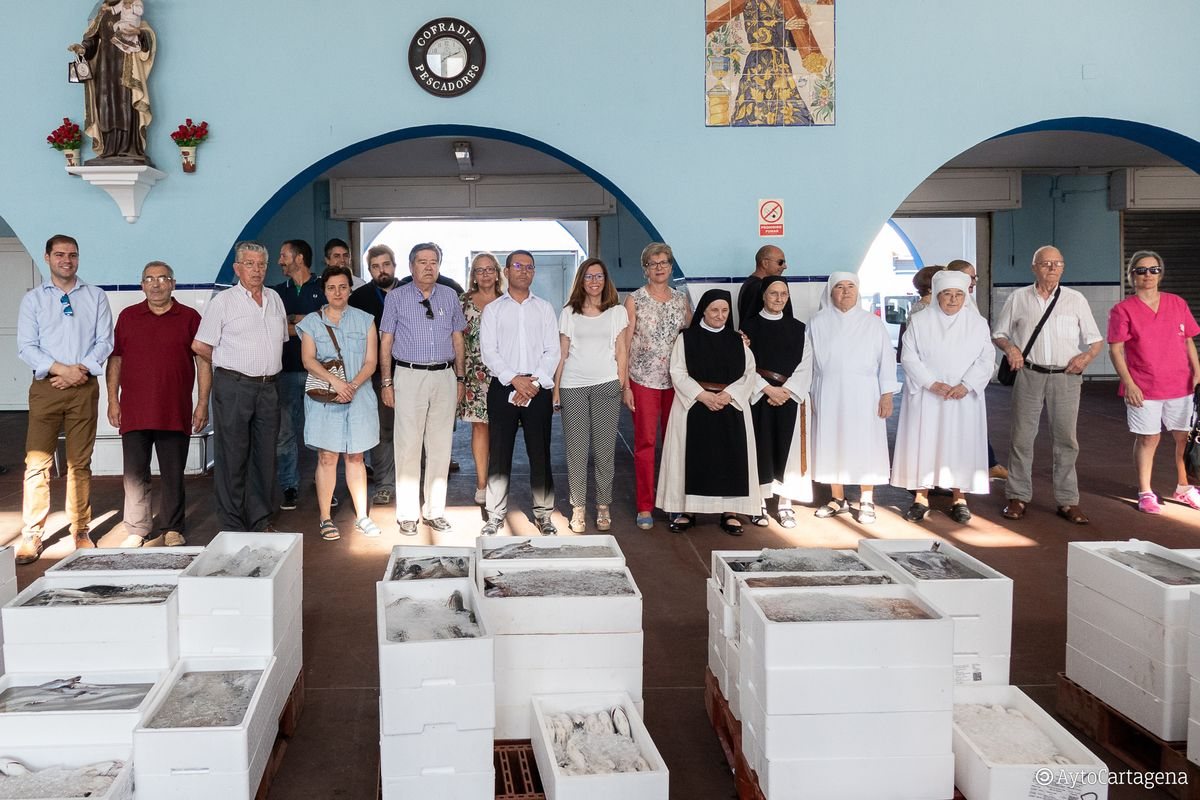 Reparto de lotes de pescado, en la lonja de Santa Lucía, a las entidades benéficas por el Día del Carmen
