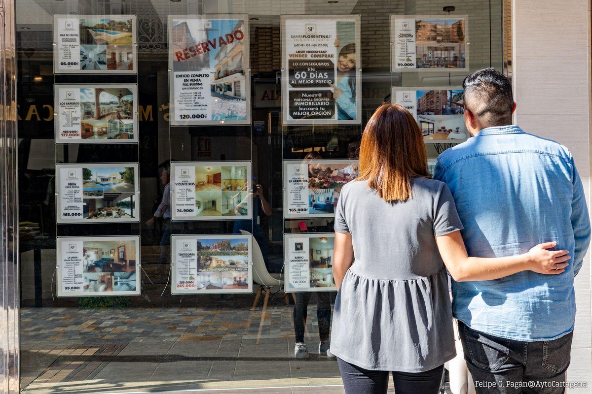 Jóvenes observan las ofertas de viviendas en una inmobiliaria